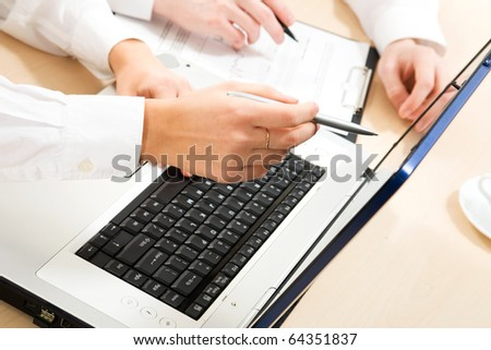 Close-up business man hands showing something on laptop to his colleague