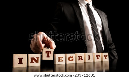 Close up Businessman Arranging Small Wooden Pieces with Integrity Letters on Black Background. - stock photo