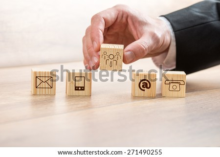 Close up Businessman Arranging Wooden Cubes with Contact and Customer Care Symbols on Top of a Table. - stock photo