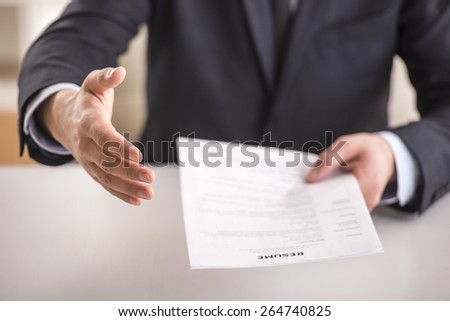 Close-up. Businessman giving prospective employee to complete a questionnaire