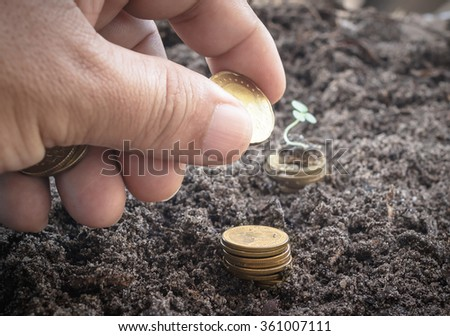 Close up businessman hand adding golden coin on stacks of coins blurred soil background. World Environment Day, Seedling concept.