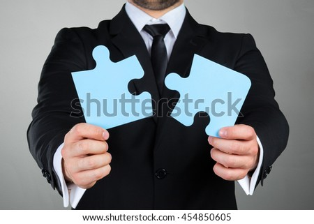 Close up Businessman Hand Holding Puzzle Piece