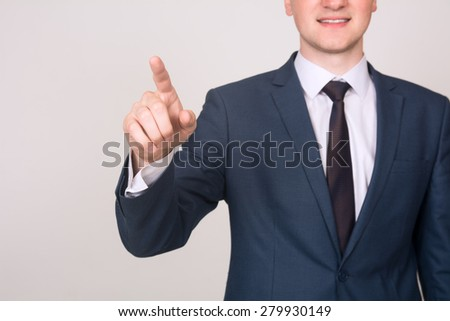 Close-up businessman hand pushing screen on light background. Selective focus on the finger. - stock photo