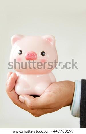 Close up businessman holding piggy bank - stock photo