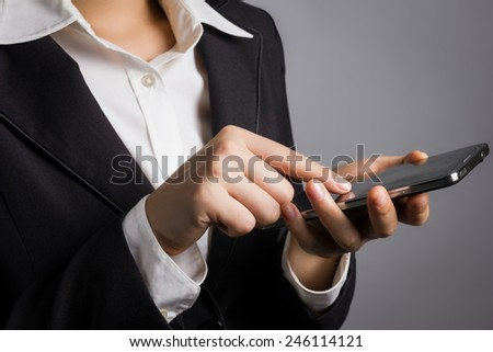 Close up businessman in black suit with hand touching smart phone.