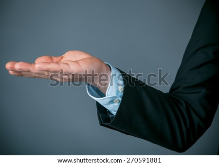 Close up Businessman in Business Suit Opening his Right Hand to his Side, Emphasizing Promoting Something with Copy Space on a Gray Background. - stock photo