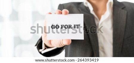 Close up Businessman Showing Conceptual Go For it Message on a Small White Card. - stock photo