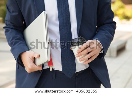 Close up businessman taking coffee break with laptop computer outdoors - stock photo