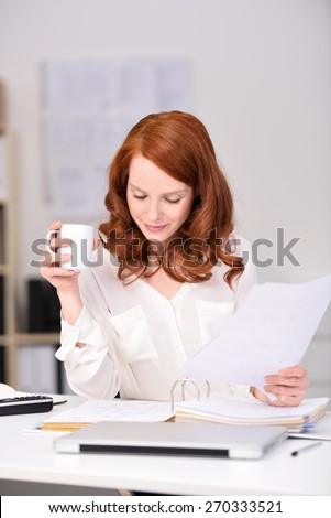 Close up Busy Young Pretty Office Woman Reading Documents While Holding a Cup of Coffee at her Office. - stock photo