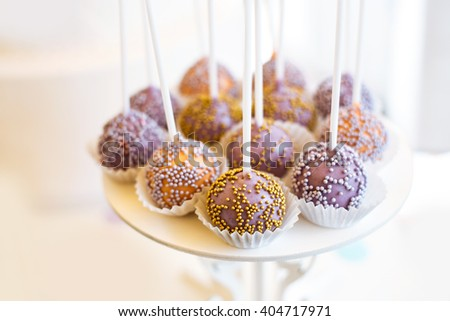 close-up cake pops decorated with sprinkles on wedding dessert table in restaurant on white background - stock photo