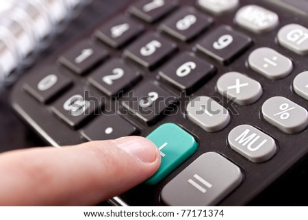 close up,  calculator and finger pressing button of the calculator - stock photo