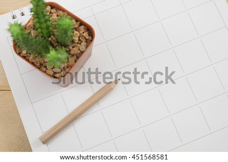 close up calendar date  and pencil with blur cactus  - stock photo