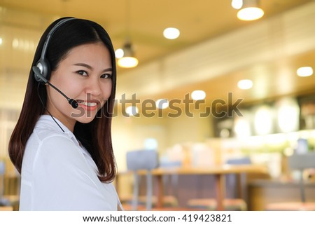 close up call center woman with earphones talking on blurred restaurant cafe bar background:food delivery concept:receptionist employee - stock photo