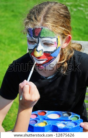 close-up candid portrait of girl having face painted - stock photo