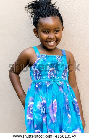 Close up candid snapshot of Laughing african girl in front of wall outdoors. - stock photo