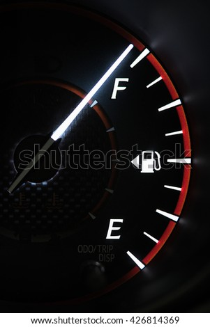 Close-up car dash board petrol meter, fuel gauge, on black background with over full gasoline in car or vehicle. - stock photo