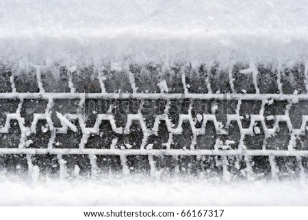 Close-up car tire tracks in the snow - stock photo