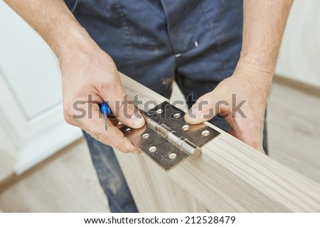 Close-up carpenter process of wood door hinge installation. - stock photo