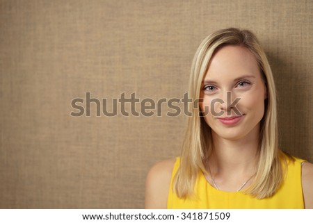 Close up Charming Blond Young Woman Smiling at the Camera Against Brown Wall Background with Copy Space. - stock photo