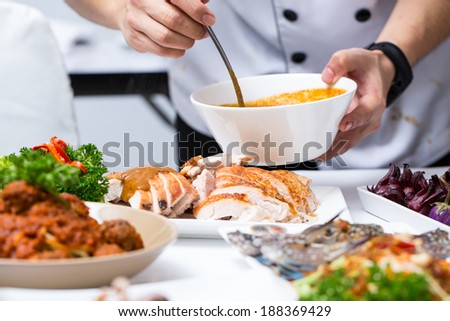 Close up Chef apply chicken soup to Roast Turkey in restaurant
