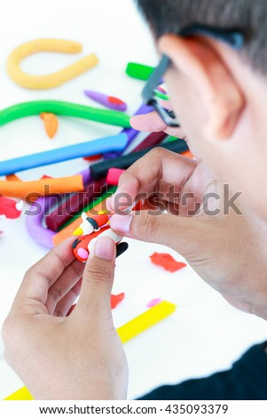 Close up. Child playing and creating toys from play dough. Selective focus, model clay in focus. Strengthen the imagination of child. - stock photo