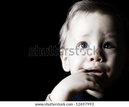 Close up child portrait on black background - stock photo