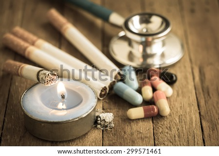 Close up cigarette,candle,Stethoscope and medicine on wooden background - stock photo