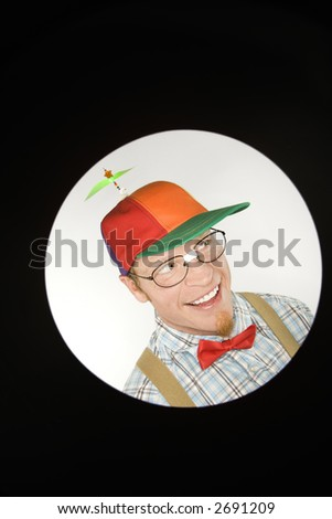 Close up circle vignett of Caucasian young man dressed like nerd wearing propeller hat looking mischievous. - stock photo