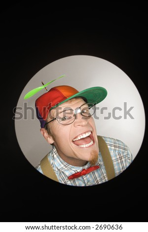 Close up circle vignette of Caucasian young man dressed like nerd wearing propeller cap with mischievous look. - stock photo