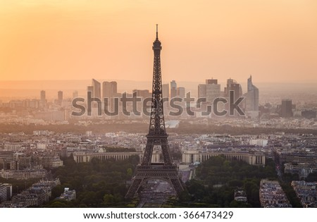 Close up cityscape capture of the Eiffel Tower and the city of Paris, France with golden sunset light in the sky and the new skyscrapers in the distance