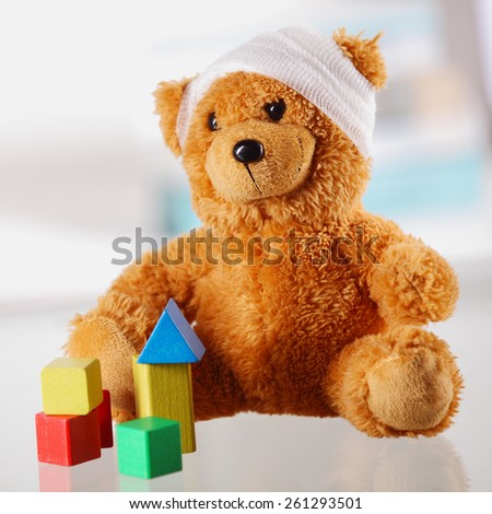 Close up Classic Brown Teddy Bear with Bandage on the Head Sitting on the Table with Assorted Block Shapes. - stock photo