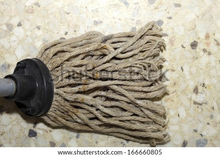 Close up cleaning the floor with a old mop, mopping housework - stock photo