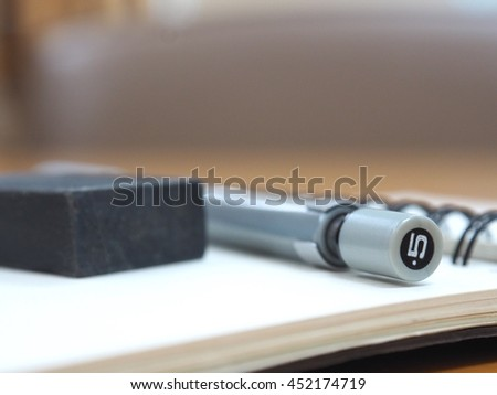 Close up clutch-type pencil and eraser black with open sketchbook or notebook, blurred background