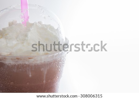 close-up cocoa milkshake topping with whipping cream in takeaway cup isolated on white background
