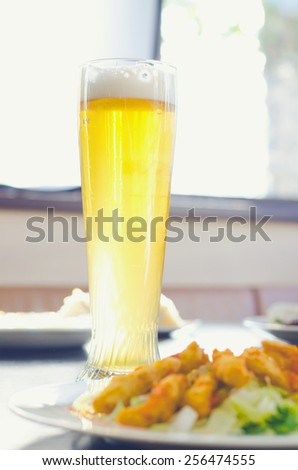 Close up Cold Beer on Long Elegant Glass Served on the Table Together with Main Dish at the Restaurant. - stock photo