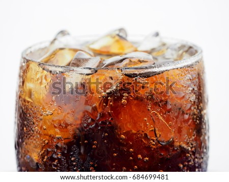 Close up cold cola in glass with ice and bubble on white background.isolated