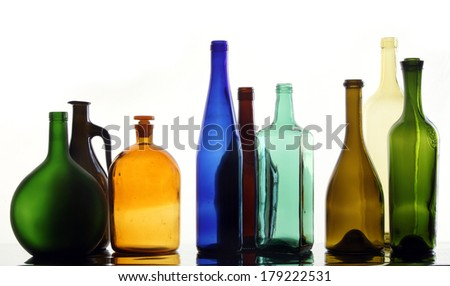 close-up collection of beautiful colored bottles of different shapes on a white background studio