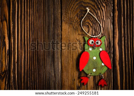 Close up Colored Wooden Owl Hanging Decoration on Top of Wooden Table, Emphasizing Copy Space. - stock photo