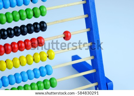 Close up colorful abacus, traditional abacus in front of gray background. Selective focus and copy space.