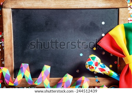 Close up Colorful Carnival Paper Streamers, Whistle and Ribbon in Front Empty Black Board. Emphasizing Copy Space. - stock photo
