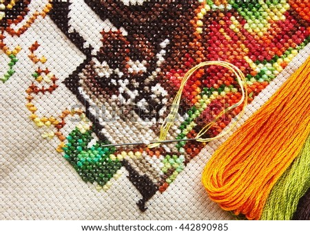 Close-up colorful  cross-stitch embroidery. Cross stitch, needle and thread - stock photo