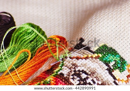 Close-up colorful  cross-stitch embroidery. Cross stitch, needle and thread. Selective focus with extreme shallow depth of field. - stock photo