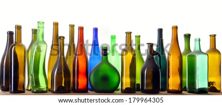 close-up colorful dusty bottles in various shapes standing on a wooden board in a studio on background white soft light