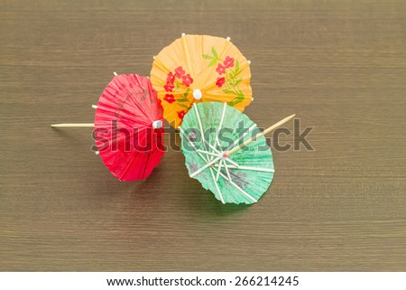 Close up colorful of many  cocktail umbrellas on black wooden  background - stock photo