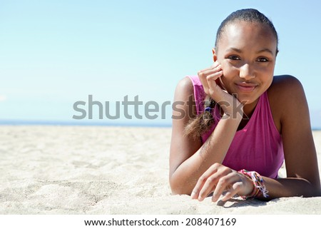 Close up colorful spacious portrait of a beautiful african american young woman relaxing on a white sand beach, smiling against a sunny blue sky on holiday. Travel and healthy lifestyle. - stock photo