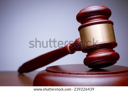 Close Up Conceptual Brown Wooden Gavel with Gold Plate Resting on the Table with Gradient Gray Brown Background. - stock photo