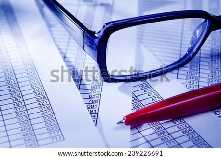 Close up Conceptual Unisex Eyeglasses and Red Pen on Top of Business Sales Documents. - stock photo