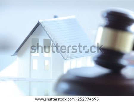 Close up Conceptual White Miniature House on Top of the Table Beside Court Gavel. - stock photo