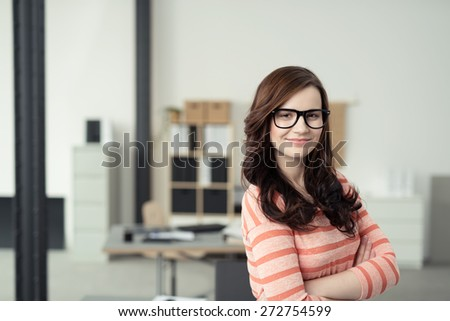 Close up Confident Attractive Young Woman Wearing Stripe Shirt and Eyeglasses Smiling at the Camera with Arms Crossing In Front of her Body. - stock photo