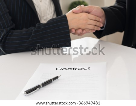 Close-up contract document with image of a firm handshake between two business partners signing a contract in background. - stock photo